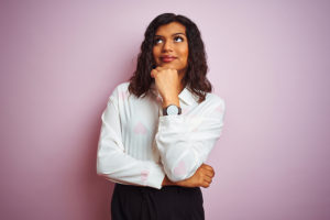 Transsexual transgender businesswoman standing over isolated pink background with hand on chin thinking about question, pensive expression. Smiling with thoughtful face. Doubt concept.