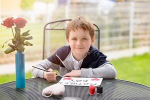 """Little 7 year old boy paints greeting card for Mom on Mother's Day with the inscription """"Mother's Day"""". Outdoors. Mother's Day"""