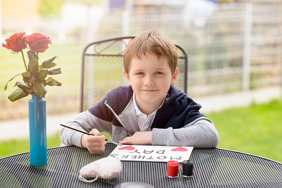 "Little 7 year old boy paints greeting card for Mom on Mother's Day with the inscription ""Mother's Day"". Outdoors. Mother's Day"
